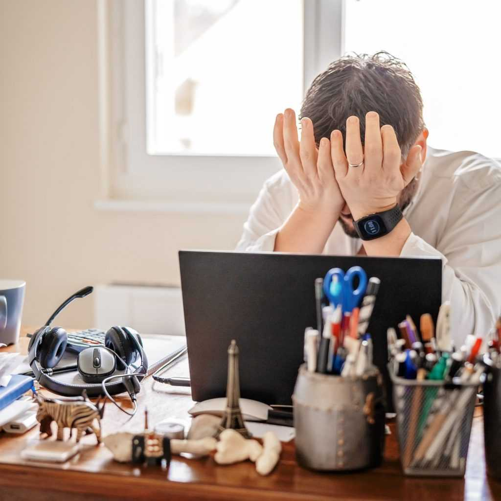 Tired frustrated businessman working from home online sitting at home office with laptop during